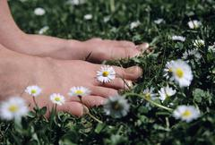 Feet on grass with daisy flowers, close-up Stock Photos