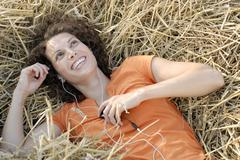 Stock Photo of Young woman with MP3 player  relaxing in hay, smiling, portrait