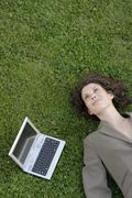 Young Business woman lying on a lawn with a laptop beside her, elevated view, Stock Photos