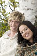 Stock Photo of young couple leaning on tree trunk, smiling