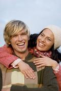 Stock Photo of young couple, man giving woman piggyback
