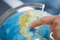 Person pointing at a globe Stock Photos