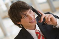 Young businessman using phone, portrait Stock Photos