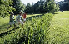 Four young people running through garden - stock photo