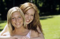 Stock Photo of Two young women embracing in garden, close-up, portrait