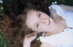 Young woman with daisy in mouth lying on grass, close-up, portrait Stock Photos