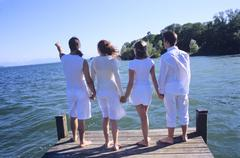 Four young people standing on jetty, holding hands, rear view - stock photo