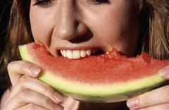 Young woman eating water melon, close-up - stock photo