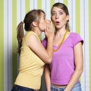 Teenage girls (16-17) whispering, portrait Stock Photos