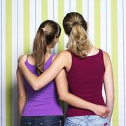 Stock Photo of Two teenage girls (16-17) embracing, rear view