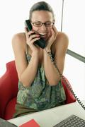 Young woman on phone in office, laughing Stock Photos