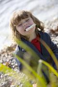 Stock Photo of Germany, Bavaria, Ammersee, little girl (3-4) bread in mouth