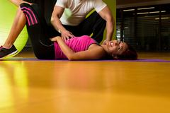 instructor assisting woman in doing sit-ups at gym - stock photo
