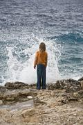 Croatia, Korcula, Girl (8-9) standing by sea looking at splashing wave, rear - stock photo