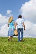 couple carrying picnic basket - stock photo