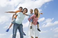 Parents carryig sons piggyback Stock Photos