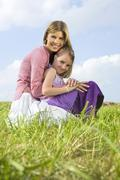 mother and daughter, crouching - stock photo