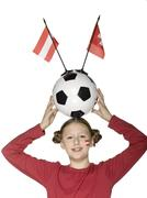 girl (10-12) holding football above her head, two flags aside - stock photo