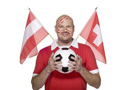 Man with austrian flag painted on face, austrian and swiss flag aside Stock Photos
