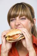 Young woman eating hamburger - stock photo