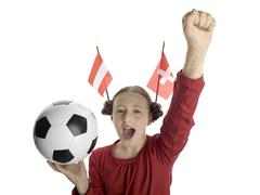 Stock Photo of girl holding football with austrian and swiss flag aside, portrait