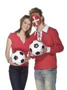 Young couple with swiss and austrian flag painted on face Stock Photos