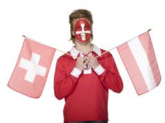 Stock Photo of man with swiss flag painted on face, holding austrian and swiss flag