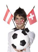 Young man with swiss flag painted on face and holding football Stock Photos