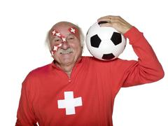 Senior man with swiss flag painted on face and carrying football on shoulders Stock Photos