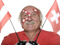Senior man with swiss flag painted on face holding football Stock Photos