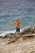Croatia, Korcula, Girl (8-9) standing by sea, smiling, portrait - stock photo