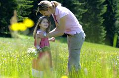 Mother and daughter in summer meadow Stock Photos