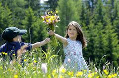 Girl and little boy with bunch of flowers in summer meadow - stock photo
