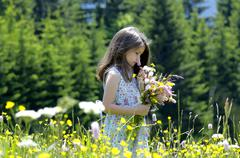 Girl with bunch of flowers in summer meadow - stock photo