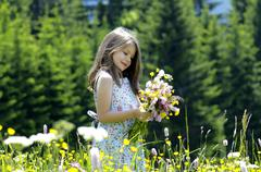 Stock Photo of Girl with bunch of flowers in summer meadow