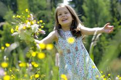 Girl with bunch of flowers in summer meadow Stock Photos