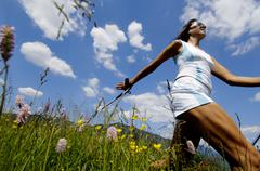 Young woman Nordic walking in meadow, Germany, low angle view - stock photo
