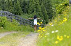 Woman in meadow with arms out, rear view - stock photo