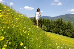 Young woman walking with ski pole in meadow Stock Photos