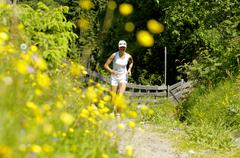 Stock Photo of Young woman jogging in meadow, smiling