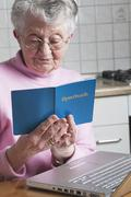Germany, Senior woman holding savings book - stock photo