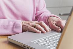 Germany, Senior woman using laptop, mid section - stock photo