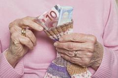 Germany, Senior woman counting money from money sock, mid section Stock Photos