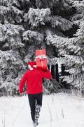 Belgium, Wallonia, High Venn, Man carrying christmas present and walking in snow - stock photo