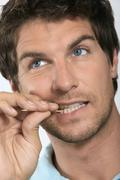 Young man holding toothpick between teeth, close-up Stock Photos