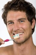 Young man holding tooth brush, portrait - stock photo