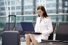 Business woman sitting in airport lounge, using laptop Stock Photos