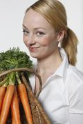 Stock Photo of Young woman holding bunch of carrots, portrait