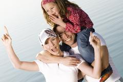 Man carrying daughter on shoulder, women standing by Stock Photos