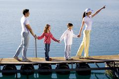Family standing in a row, holding hands. Stock Photos